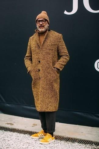 """Модные мужские луки 2020 фото: Дуэт светло-коричневого длинного пальто с узором """"в ёлочку"""" и темно-серых шерстяных брюк чинос позволит реализовать в твоем образе городской стиль современного парня. Ты можешь легко адаптировать такой ансамбль к повседневным нуждам, завершив его желтыми замшевыми низкими кедами."""