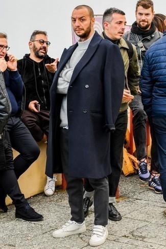Темно-синее длинное пальто: с чем носить и как сочетать: Темно-синее длинное пальто в паре с темно-серыми брюками чинос — нескучный лук для молодых людей, работающих в офисе. Создать красивый контраст с остальными составляющими этого ансамбля помогут белые кожаные низкие кеды.