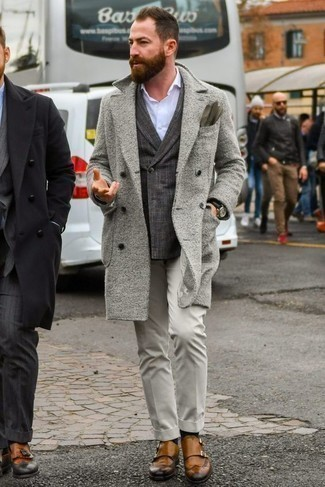 Модные мужские луки 2020 фото в прохладную погоду: Сочетание серого длинного пальто и серых классических брюк поможет составить модный и в то же время изысканный лук. Такой лук несложно адаптировать к повседневным условиям городской жизни, если надеть в сочетании с ним светло-коричневые кожаные монки с двумя ремешками.