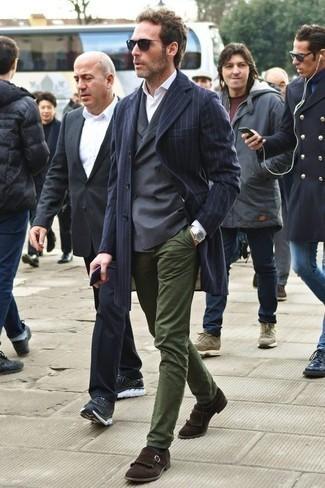 Модные мужские луки 2020 фото в прохладную погоду: Лук из темно-синего длинного пальто в вертикальную полоску и оливковых брюк чинос позволит выглядеть по моде, а также выразить твой личный стиль. Темно-коричневые замшевые лоферы c бахромой добавят луку немного консерватизма.