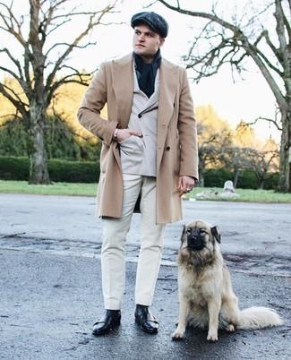 Мужские луки зима: Сочетание светло-коричневого длинного пальто и белых брюк чинос поможет выглядеть по моде, но при этом выразить твой индивидуальный стиль. Черные кожаные повседневные ботинки чудесно впишутся в лук. Подобный лук несомненно поможет пережить студеную зиму.