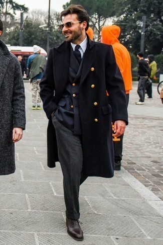 Темно-серые классические брюки: с чем носить и как сочетать мужчине: Несмотря на то, что этот образ кажется довольно-таки выдержанным, дуэт темно-синего длинного пальто и темно-серых классических брюк всегда будет по душе стильным молодым людям, но также пленяет при этом дамские сердца. Темно-коричневые кожаные оксфорды великолепно дополнят этот ансамбль.