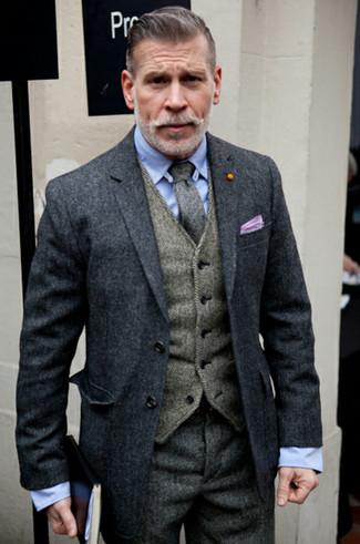 """Как Nick Wooster носит Темно-серое длинное пальто, Серый шерстяной жилет с узором """"в ёлочку"""", Голубая классическая рубашка, Темно-серые шерстяные классические брюки с узором """"в ёлочку"""""""