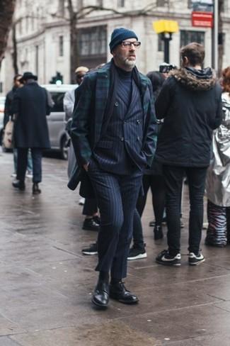 Как одеваться мужчине за 40: Несмотря на то, что этот образ выглядит довольно-таки выдержанно, тандем темно-сине-зеленого длинного пальто в шотландскую клетку и темно-синего костюма в вертикальную полоску всегда будет нравиться джентльменам, неизбежно пленяя при этом сердца прекрасных дам. Весьма выигрышно здесь будут выглядеть черные кожаные броги.