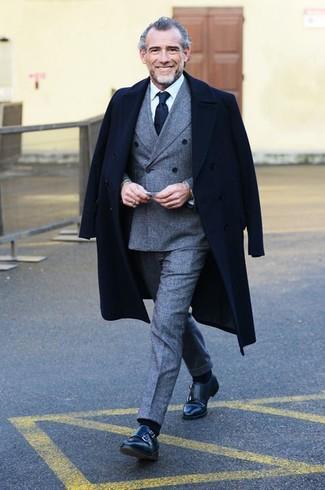 Черное длинное пальто в сочетании с серым шерстяным костюмом позволит создать стильный и мужественный лук. Почему бы не добавить в этот образ чуточку небрежности с помощью черных кожаных монок с двумя ремешками?