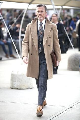 Несмотря на то, что это довольно сдержанный ансамбль, сочетание светло-коричневого длинного пальто и темно-синего костюма в клетку всегда будет по душе стильным мужчинам, неминуемо пленяя при этом дамские сердца. Что же до обуви, светло-коричневые кожаные монки с двумя ремешками — самый целесообразный вариант.