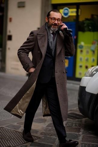 """Как одеваться мужчине за 40: Несмотря на то, что этот ансамбль кажется весьма выдержанным, лук из темно-коричневого длинного пальто с узором """"в ёлочку"""" и темно-синего костюма в вертикальную полоску неизменно нравится стильным мужчинам, а также покоряет сердца представительниц прекрасного пола. Вместе с этим ансамблем чудесно будут смотреться темно-коричневые замшевые лоферы с кисточками."""