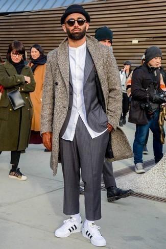"""Темно-коричневые солнцезащитные очки: с чем носить и как сочетать мужчине: Если в одежде ты ценишь удобство и функциональность, коричневое длинное пальто с узором """"в ёлочку"""" и темно-коричневые солнцезащитные очки — превосходный вариант для расслабленного мужского лука на каждый день. Теперь почему бы не привнести в этот ансамбль на каждый день чуточку изысканности с помощью бело-черных кожаных низких кед?"""