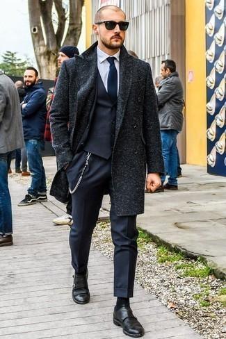 Темно-синий костюм-тройка: с чем носить и как сочетать: Несмотря на то, что это весьма сдержанный образ, образ из темно-синего костюма-тройки и темно-синего длинного пальто всегда будет по душе стильным молодым людям, неминуемо покоряя при этом сердца женского пола. Закончив лук черными кожаными монками с двумя ремешками, ты привнесешь в него немного непринужденности.