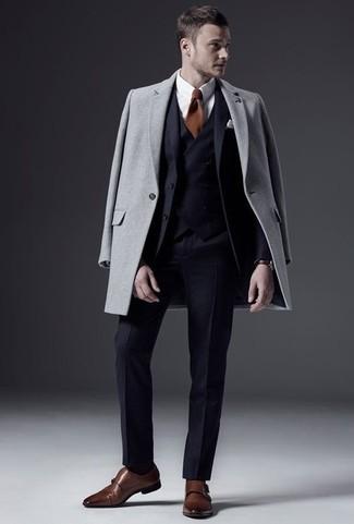 Темно-синий костюм-тройка: с чем носить и как сочетать: Несмотря на то, что этот образ выглядит довольно-таки сдержанно, ансамбль из темно-синего костюма-тройки и серого длинного пальто всегда будет нравиться стильным мужчинам, но также пленяет при этом сердца девушек. Создать красивый контраст с остальными составляющими этого лука помогут коричневые кожаные монки с двумя ремешками.
