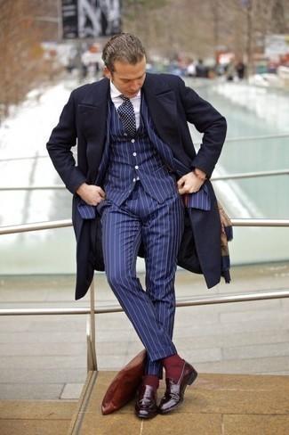 Темно-синее длинное пальто: с чем носить и как сочетать: Несмотря на то, что это классический образ, ансамбль из темно-синего длинного пальто и темно-синего костюма-тройки в вертикальную полоску приходится по вкусу стильным молодым людям, покоряя при этом сердца девушек. Подбирая обувь, можно немного поэкспериментировать и завершить образ темно-красными кожаными лоферами.