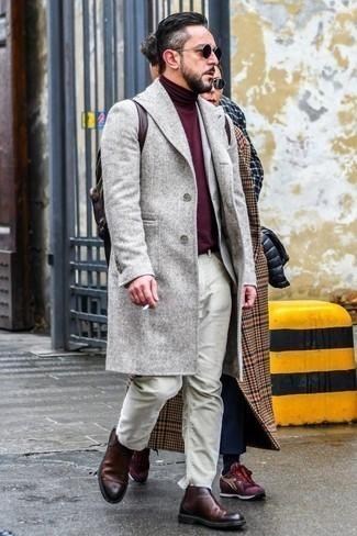 Модные мужские луки 2020 фото в прохладную погоду: Серое длинное пальто и бежевые джинсы — замечательное решение для мероприятий с дресс-кодом смарт-кэжуал. Хотел бы сделать ансамбль немного строже? Тогда в качестве обуви к этому образу, стоит обратить внимание на темно-красные кожаные ботинки челси.