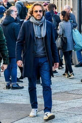 Модные мужские луки 2020 фото зима 2021: Комбо из темно-синего длинного пальто и темно-синих джинсов поможет создать стильный, и в то же время мужественный образ. Создать запоминающийся контраст с остальными вещами из этого лука помогут бело-темно-синие кожаные высокие кеды. В зимнее время года хочется одеваться не только тепло, но еще и по моде. Такое сочетание вещей обязательно тебе в этом поможет.