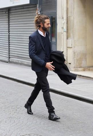 Модный лук: черное длинное пальто, темно-синий пиджак, темно-синий свитер с v-образным вырезом, белая рубашка с длинным рукавом