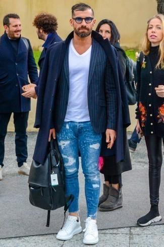 Темно-синее длинное пальто: с чем носить и как сочетать: Удобное сочетание темно-синего длинного пальто и синих рваных зауженных джинсов несомненно будет привлекать взоры прекрасных девушек. Белые кожаные низкие кеды отлично дополнят этот ансамбль.