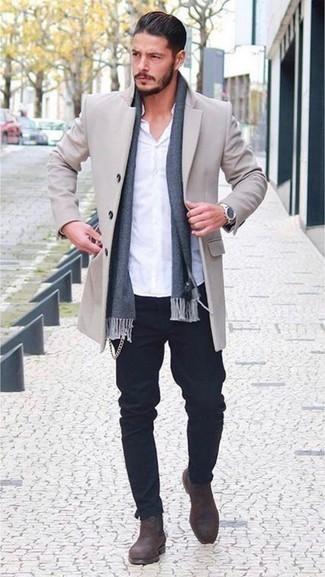 Темно-коричневые замшевые ботинки челси: с чем носить и как сочетать мужчине: Составив ансамбль из бежевого длинного пальто и темно-синих джинсов, получишь хороший мужской ансамбль для полуформальных мероприятий после работы. Теперь почему бы не добавить в повседневный образ толику консерватизма с помощью темно-коричневых замшевых ботинок челси?