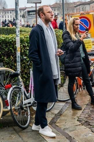 Темно-синее длинное пальто: с чем носить и как сочетать: Темно-синее длинное пальто в сочетании с темно-синими шерстяными спортивными штанами — классный вариант для создания мужского лука в элегантно-деловом стиле. Тебе нравятся незаурядные решения? Тогда дополни свой образ белыми кожаными низкими кедами.