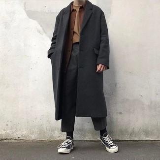 С чем носить темно-серые брюки чинос: Если ты принадлежишь к той категории мужчин, которые любят выглядеть стильно, тебе понравится сочетание темно-серого длинного пальто и темно-серых брюк чинос. Создать запоминающийся контраст с остальными предметами из этого ансамбля помогут черно-белые низкие кеды из плотной ткани.