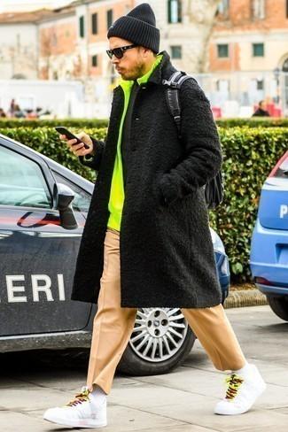 Светло-коричневые брюки чинос: с чем носить и как сочетать: Черное длинное пальто и светло-коричневые брюки чинос — великолепный выбор для создания мужского лука в элегантно-деловом стиле. Любители смелых вариантов могут закончить лук белыми кожаными низкими кедами.