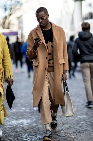 Как и с чем носить: светло-коричневое длинное пальто, черный свитер с круглым вырезом с принтом, светло-коричневые брюки чинос, черные кроссовки