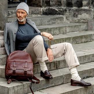 Модный лук: серое длинное пальто, темно-серый свитер с круглым вырезом, бежевые брюки чинос, темно-коричневые кожаные лоферы
