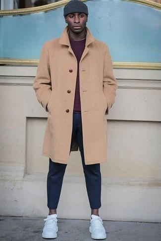 Темно-синие брюки чинос: с чем носить и как сочетать: Лук из светло-коричневого длинного пальто и темно-синих брюк чинос поможет выглядеть модно, но при этом выразить твой личный стиль. Завершив ансамбль белыми кожаными низкими кедами, ты привнесешь в него немного динамичности.