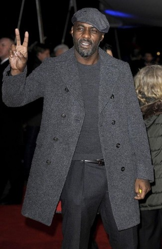 Как Idris Elba носит Темно-серое длинное пальто, Темно-серый свитер с круглым вырезом, Темно-серые шерстяные классические брюки, Темно-серая кепка