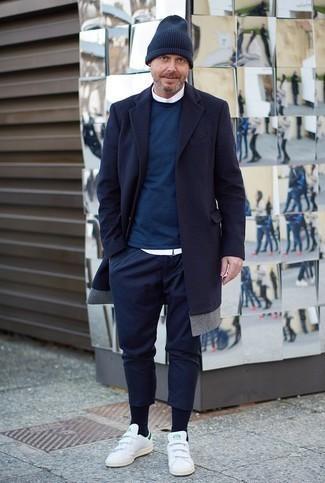 Темно-синие брюки чинос: с чем носить и как сочетать: Лук из темно-синего длинного пальто и темно-синих брюк чинос выглядит выше всяких похвал, согласен? Любители рискованных вариантов могут дополнить лук белыми кожаными низкими кедами.