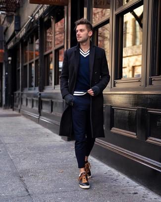 Как и с чем носить: черное длинное пальто, темно-сине-белый свитер с v-образным вырезом, темно-синие брюки чинос, черные кожаные низкие кеды