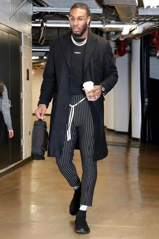 Как и с чем носить: черное длинное пальто, черно-белая футболка с круглым вырезом с принтом, черно-белые брюки чинос в вертикальную полоску, черные кроссовки