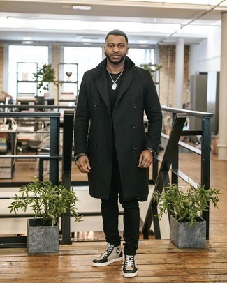 Мужские луки в прохладную погоду: Черное длинное пальто в сочетании с черными джинсами позволит подчеркнуть твой индивидуальный стиль и выигрышно выделиться из толпы. Пара бежевых кожаных высоких кед добавит облику непринужденности и беззаботства.