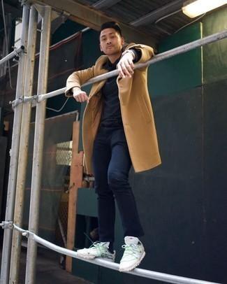 Мужские луки в холод: Сочетание светло-коричневого длинного пальто и темно-синих джинсов поможет выразить твой индивидуальный стиль и выигрышно выделиться из серой массы. Ты можешь легко приспособить такой лук к повседневным нуждам, надев белыми кроссовками.