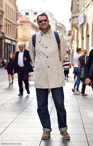 Как и с чем носить: бежевый дождевик, темно-синие джинсы, оливковые замшевые ботинки дезерты, черный кожаный рюкзак