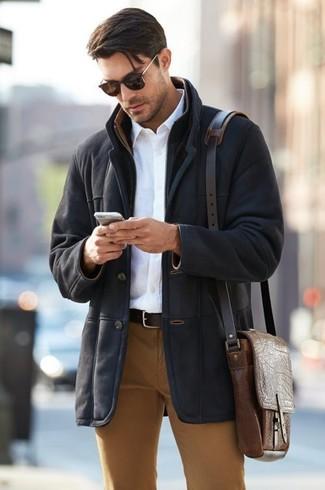 Как и с чем носить: черная дубленка, белая классическая рубашка, табачные брюки чинос, коричневая кожаная сумка почтальона