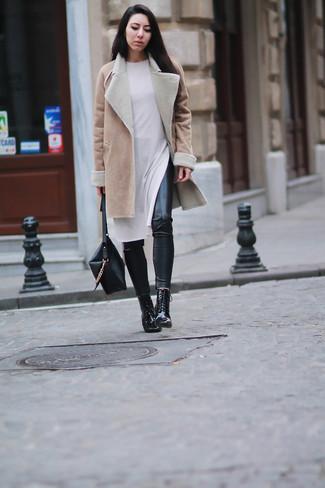 Как и с чем носить: светло-коричневая дубленка, белое платье-свитер, черные кожаные леггинсы, черные кожаные ботильоны на шнуровке