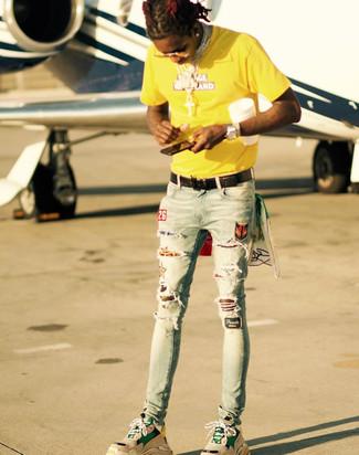 Как и с чем носить: желтая футболка с круглым вырезом с принтом, голубые рваные зауженные джинсы, светло-коричневые кроссовки, черный кожаный плетеный ремень