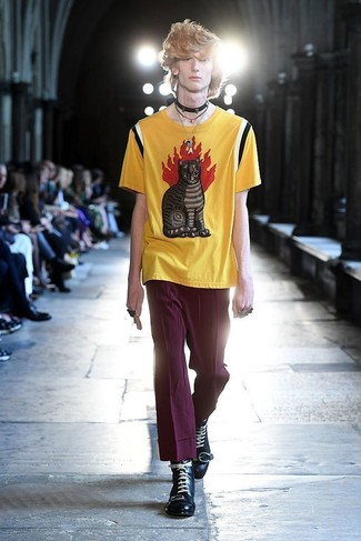 Как и с чем носить: желтая футболка с круглым вырезом с принтом, пурпурные брюки чинос, черные кожаные повседневные ботинки