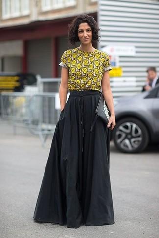 Как и с чем носить: желтая футболка с круглым вырезом с цветочным принтом, черная длинная юбка со складками, черно-белый кожаный клатч с принтом