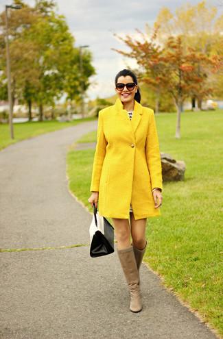 Как и с чем носить: желтое пальто, светло-коричневые кожаные сапоги, бело-черная кожаная сумка-саквояж