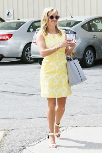 Как и с чем носить: желтое платье-футляр с принтом, белые кожаные босоножки на каблуке, серая кожаная большая сумка