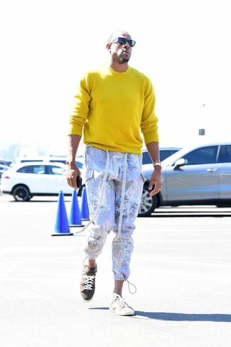 Как Andre Iguodala носит Желтый свитер с круглым вырезом, Светло-фиолетовые брюки карго с принтом, Бежевые замшевые низкие кеды, Черные солнцезащитные очки