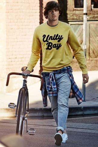 Как и с чем носить: желтый свитшот с принтом, бело-красно-синяя рубашка с длинным рукавом в шотландскую клетку, голубые джинсы, белые низкие кеды из плотной ткани