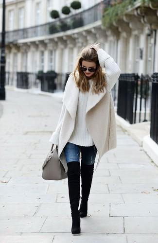 Как и с чем носить: бежевый жилет из овчины, белый вязаный свободный свитер, синие джинсы, черные замшевые ботфорты