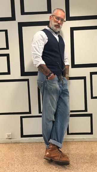 Как одеваться мужчине за 40: Темно-синий жилет в шотландскую клетку и синие рваные джинсы — обязательные предметы в гардеробе джентльменов с хорошим вкусом в одежде. Думаешь добавить сюда толику классики? Тогда в качестве обуви к этому луку, стоит выбрать коричневые кожаные повседневные ботинки.