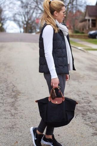 Черная большая сумка из плотной ткани: с чем носить и как сочетать: Черный стеганый жилет и черная большая сумка из плотной ткани — отличное решение для барышень, которые никогда не сидят на месте. В тандеме с этим образом наиболее гармонично смотрятся черные кроссовки.