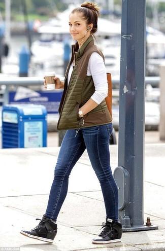 Как и с чем носить: оливковый стеганый жилет, белая футболка с длинным рукавом, синие джинсы скинни, черные замшевые кроссовки на танкетке
