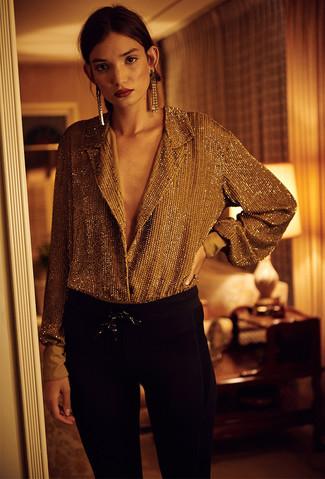 Золотая блуза на пуговицах и черные узкие брюки — наряд, который будет непременно притягивать восхищенные взгляды. Как по нам, так это крутая задумка для межсезонья, когда погода станет менее благоприятной.