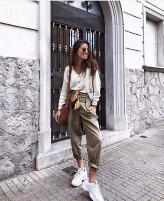 Светло-коричневые брюки-галифе: с чем носить и как сочетать женщине: Комбо из белого кардигана и светло-коричневых брюк-галифе позволит подчеркнуть твой индивидуальный стиль и выигрышно выделиться из серой массы. Такой образ несложно адаптировать к повседневным условиям городской жизни, если завершить его белыми кроссовками.