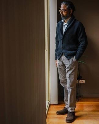 С чем носить коричневые брюки чинос: Сочетание темно-синего кардигана с отложным воротником и коричневых брюк чинос — необыденный ансамбль для рабочего дня в офисе. Что до обуви, темно-коричневые замшевые ботинки дезерты — самый удачный вариант.