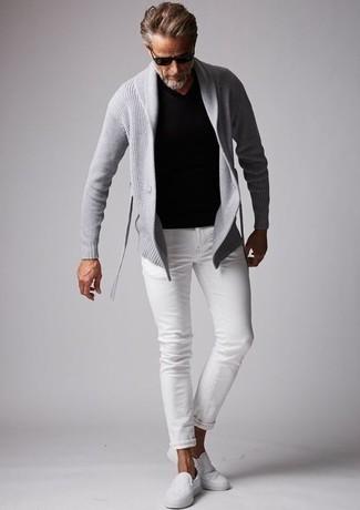 Как одеваться мужчине за 50: Серый кардиган с отложным воротником и белые джинсы — уместное тандем и для вечерних вылазок с друзьями, и для дневных поездок на выходных. В тандеме с этим ансамблем великолепно смотрятся белые слипоны из плотной ткани.